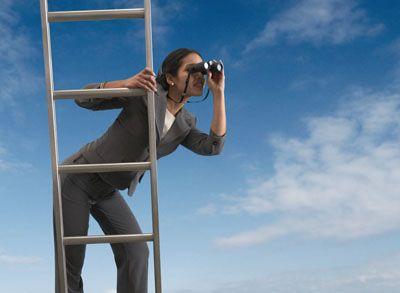 Businesswoman standing on a ladder looking through binoculars